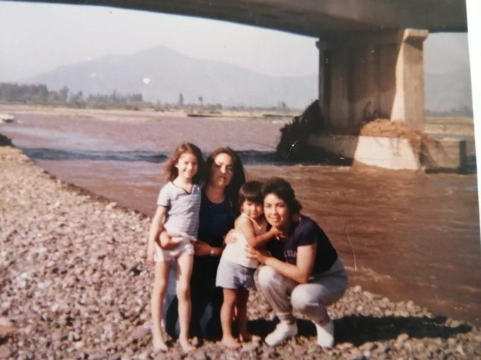Cesar Valencia, artista marika y transfronterizx del valle de Quillota, junto a sus tías Sandra, Pamela y Romina, en la ribera del rio Aconcagua. Primeras derivas a pasos de su casa en la Villa General Mackena, cuando el río no sufría aun la furia del extractivismo. Circa 1984.